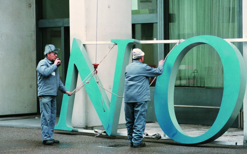 Photograph of the old Novartis logo being changed out at the Novartis St. Johann site in Basel