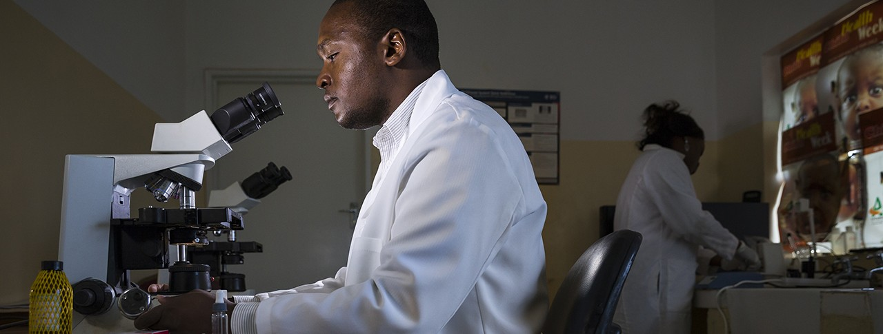 Researcher with microscope-image